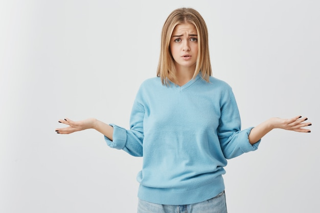Beautiful puzzled and confused young woman dressed casually exclaming in despair and shrugging shoulders in full disbelief after she received some unexpected negative news. body language