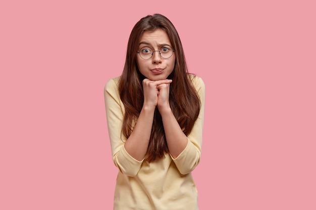 Il bellissimo modello femminile perplesso tiene le mani unite sotto il mento, ascolta attentamente le informazioni, ha un'espressione curiosa e preoccupata, indossa un maglione casual, isolato su un muro rosa. emozioni umane