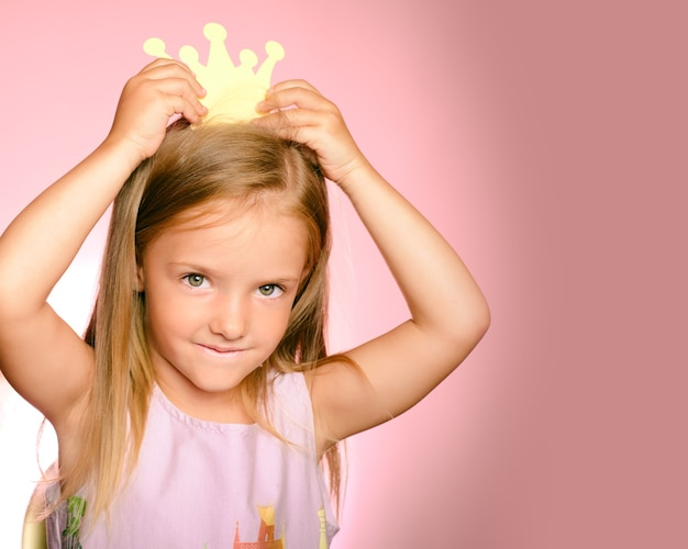 Beautiful queen in gold crown. little princess girl in yellow crown and beautiful dress on pink background.