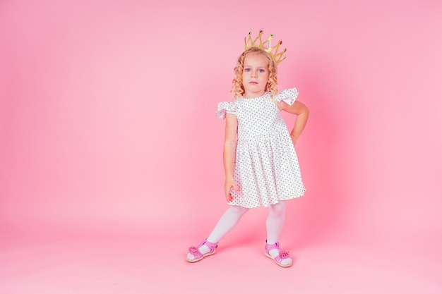 Beautiful queen in gold crown.little shopping girl in a princess fashion dress. pretty child preparing for a birthday easter party on a pink background in the studio.dancer ballerina