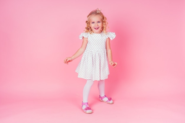 Beautiful queen in gold crown.little shopping girl in a princess fashion dress. pretty child preparing for a birthday easter party on a pink background in the studio.