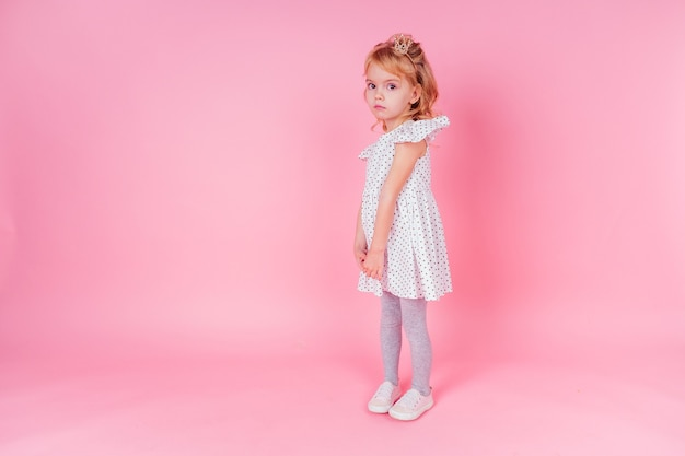 金の王冠の美しい女王。プリンセスファッションドレスの小さなショッピングの女の子。スタジオでピンクの背景に誕生日イースターパーティーの準備をしているかわいい子。