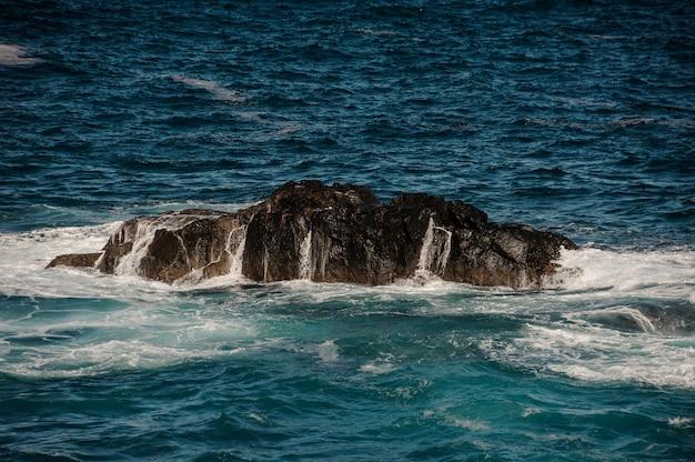 Красивое бушующее глубокое море с белыми волнами и пеной вокруг скалы в солнечный день