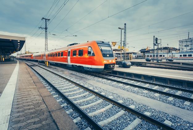 현대 고속 빨간 통근 열차와 아름다운 기차역. 빈티지 토닝과 철도. 철도 플랫폼에서 기차. 산업 개념