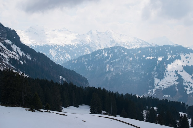Beautiful range of high rocky mountains covered with snow under a cloudy sky