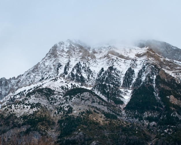 Beautiful range of high rocky mountains covered with snow during daytime