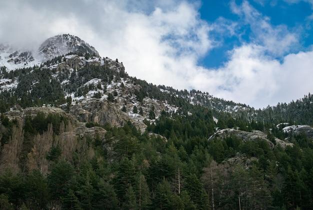 Красивая гряда высоких скалистых гор, покрытых снегом в дневное время.