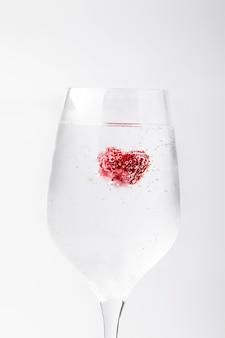 Beautiful raspberry in a water with bubbles in a wine glass. abstract