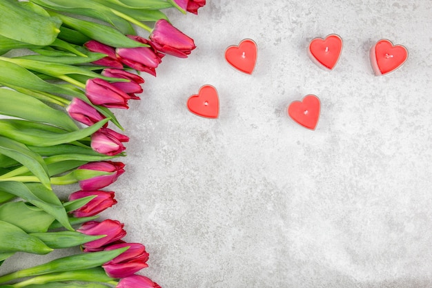 Beautiful red bouquet of tulips and red candles in the form of a heart on a gray concrete.