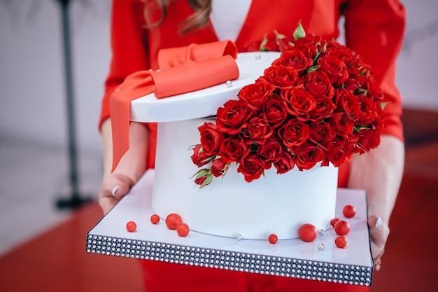 Красивый красный торт с луком и розами держал в руках на день рождения.