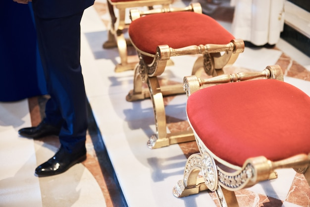 Beautiful red chairs for bride and groom in a church.