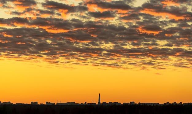 Красивые красные облака, освещенные лучами солнца на закате, плывут по золотому небу.