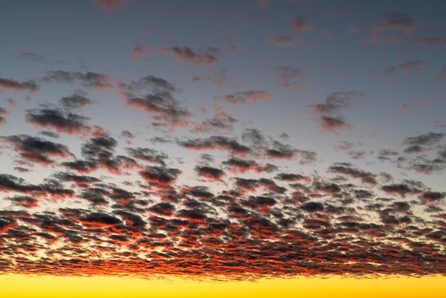 Красивые красные облака, освещенные лучами солнца на закате, плывут по желто-голубому небу.