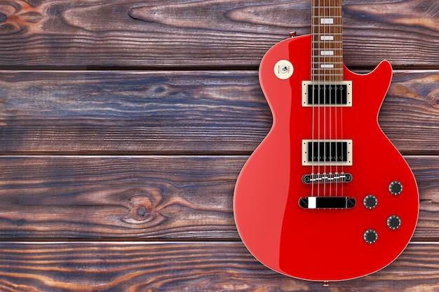 나무 테이블에 복고 스타일의 아름 다운 빨간 일렉트릭 기타. 3d 렌더링