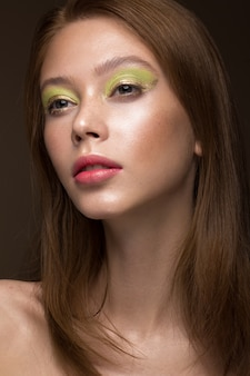 Beautiful red-hair girl with creative green makeup