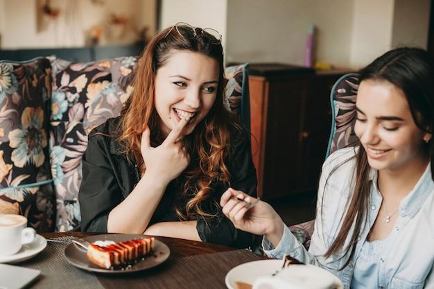 コーヒーショップに座っている彼女のガールフレンドを見ながら彼女の指でケーキを味わいながら笑っている美しい赤い髪の女性。