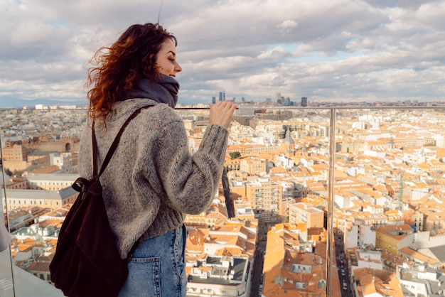 Beautiful red hair woman with cheerful smile sightseeing madrid skyline from a rooftop in a hotel