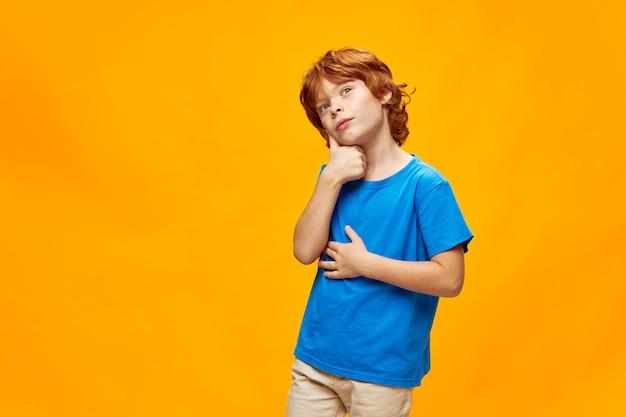Красивый рыжеволосый мальчик задумчивое выражение лица держать руку возле головы мечтательный взгляд синяя футболка