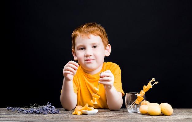 맛있는 슬라이스 복숭아와 함께 아름 다운 빨간 머리 소년
