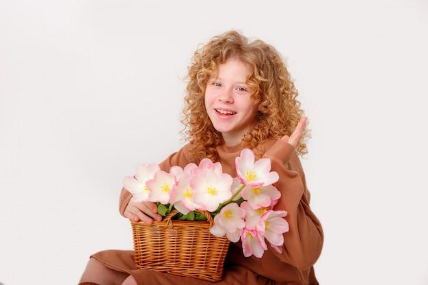 白地にピンクの春のチューリップの花束を持つ美しい赤い髪の巻き毛の十代の少女