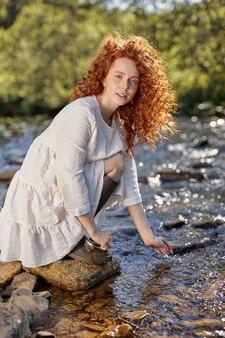 自然の中で、水に触れる川の横に座っている美しい赤毛の巻き毛の女性