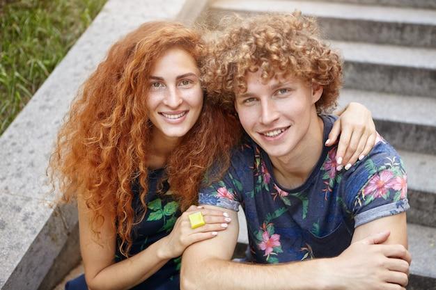 彼女のボーイフレンドを抱きしめる美しい赤髪の女性