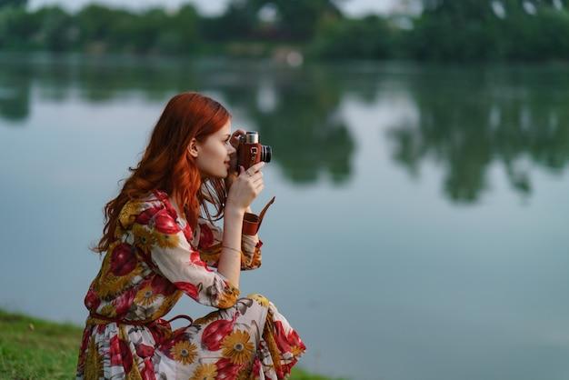 Красивая рыжеволосая женщина-фотограф снимает со старой камерой