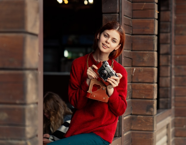 Beautiful red-haired female photographer takes pictures with an old camera
