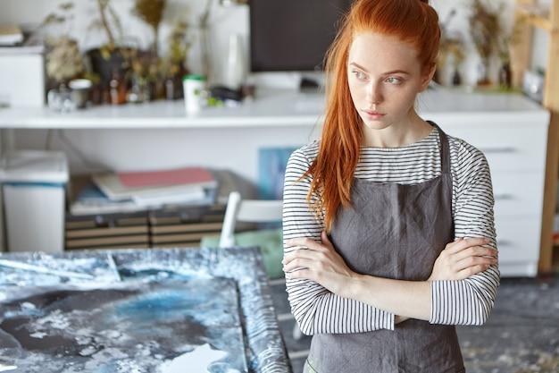 美しい赤髪の女性がエプロンを着て、手を組んで、しんみりと脇を見ながらワークショップに立ち、傑作を作った後しばらく休んでいます。創造的な生姜の若い女性