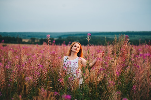 Beautiful red-haired girl in a dress in a flowering field of willow-tea.