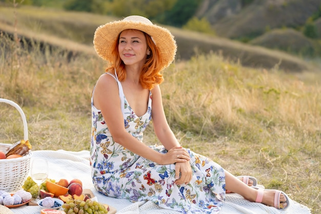 美しい赤毛の少女は、自然に沈む夕日を楽しんでいます。フィールドでのピクニック。