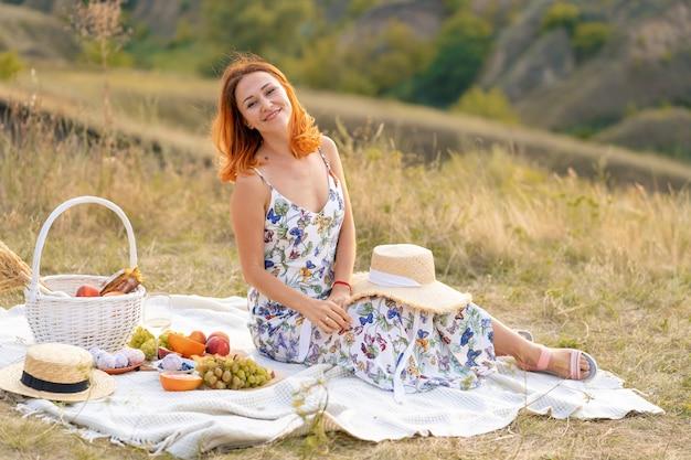 美しい赤毛の少女は、自然に沈む夕日を楽しんでいます。