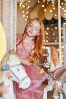 Beautiful red-haired girl long hair rides carousel