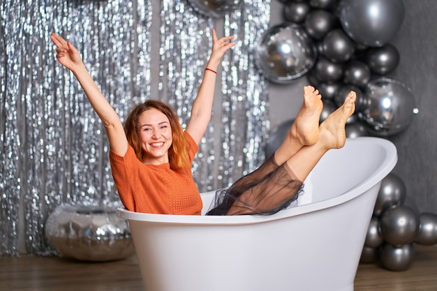 The beautiful red-haired girl rejoices sitting dressed in the bath. against tinsel and balloons. success concept.