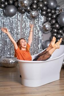 美しい赤毛の女の子はお風呂に身を包んで座って喜ぶ。風船を背景に