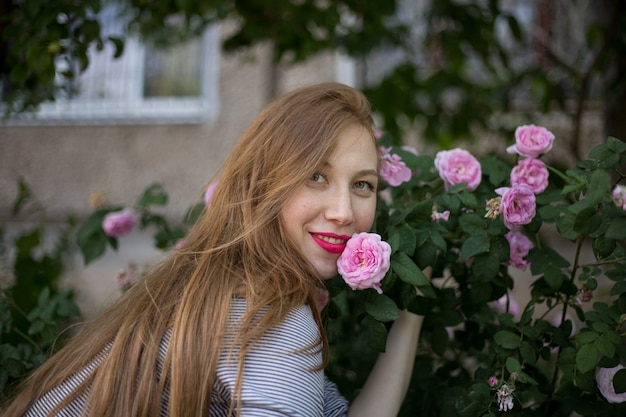 Beautiful red-haired girl sitting alone near a bush of pink roses and smiling