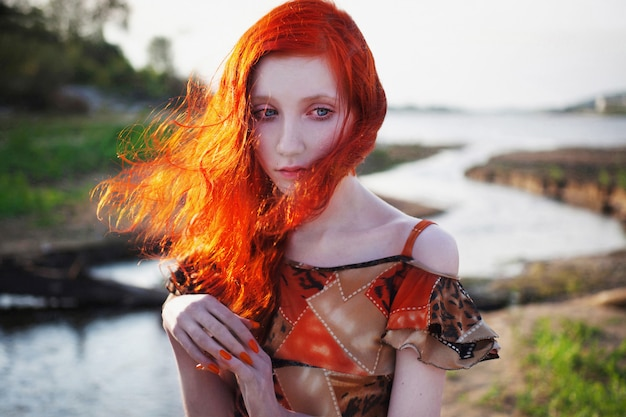 Beautiful red-haired girl in sundress standing on the background of the river,