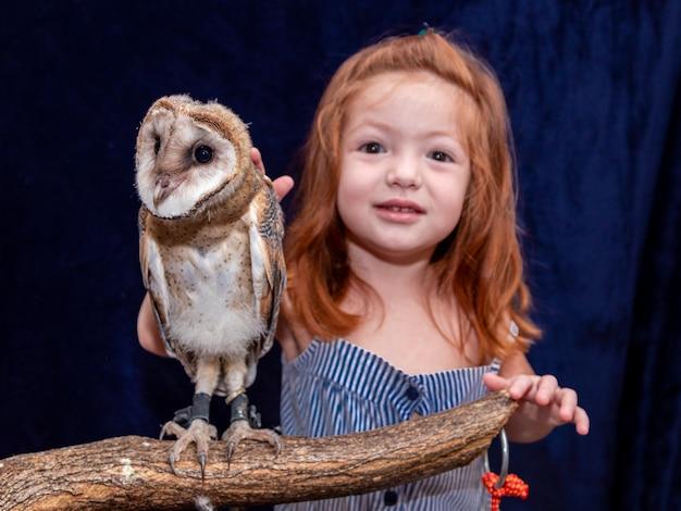 ペットのフクロウと一緒に写真を撮る美しい赤毛の少女。
