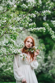 Beautiful red-haired girl in a white dress among blossoming apple-trees in the garden.