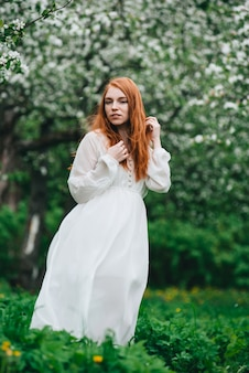 Beautiful red-haired girl in a white dress among blossoming apple trees in the garden