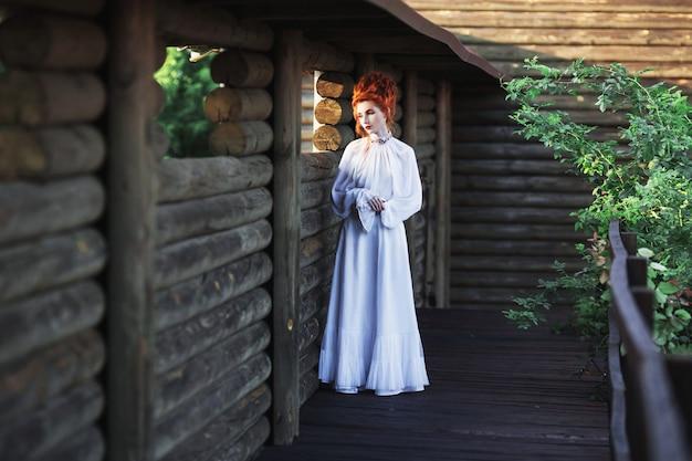 公園の古い白いドレスに高い髪の美しい赤い髪の少女。ビクトリア朝時代。歴史的な衣装。ホワイトクイーン。プリンセス城