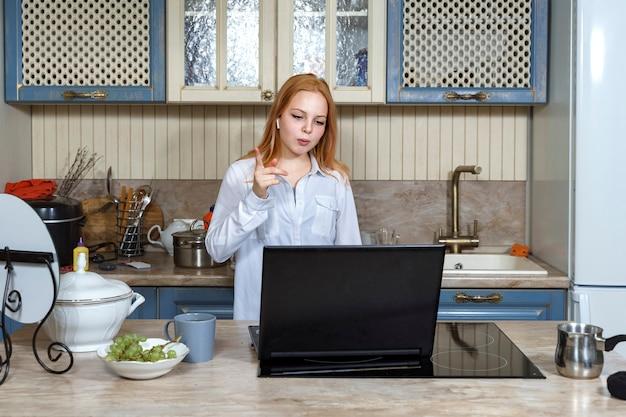 キッチンにノートパソコンを持っている美しい赤毛の女の子が彼女のフードブログのためにオンラインでストリーミングしています