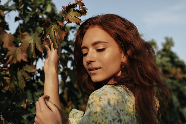 Beautiful red haired girl with freckles in yellow and green cool outfit looking down and posing on vineyards