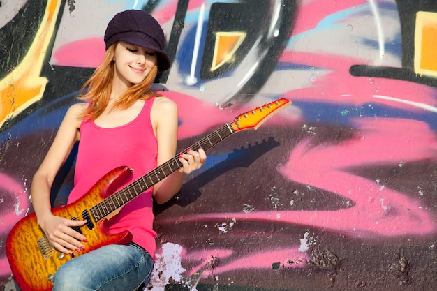 기타와 낙서 벽을 가진 아름 다운 빨간 머리 소녀