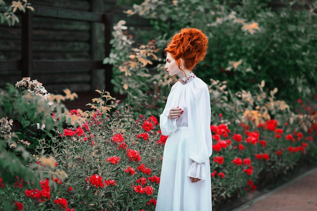 Beautiful red-haired girl with a high hair in an old white dress in the park. the victorian era. historic costume. white queen. princess castle