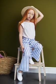 長い髪と美しい大きな青い目を持つ美しい赤い髪の少女。オリーブ色の背景にポーズをとって夏服で赤毛の女児。真っ赤な髪のノルウェーの女の子