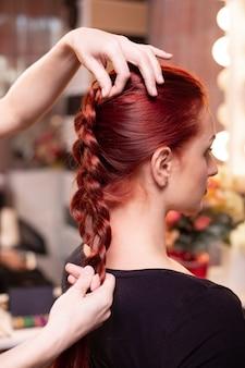 美容院で、長い髪の美しい赤毛の女の子、美容師がフレンチブレイドを織ります