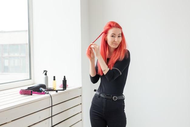 長い髪の美しい赤毛の女の子は、美容院で三つ編みを織ります。プロフェッショナル