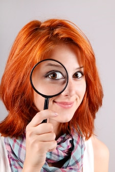 Beautiful red-haired girl with loupe zooming her eye.