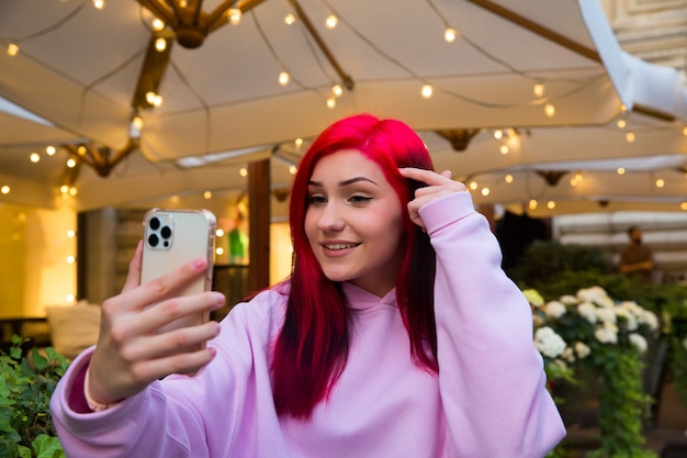 Beautiful red-haired influencer blogger girl in cafe talking making video call using smartphone with her subscribers in social networks.